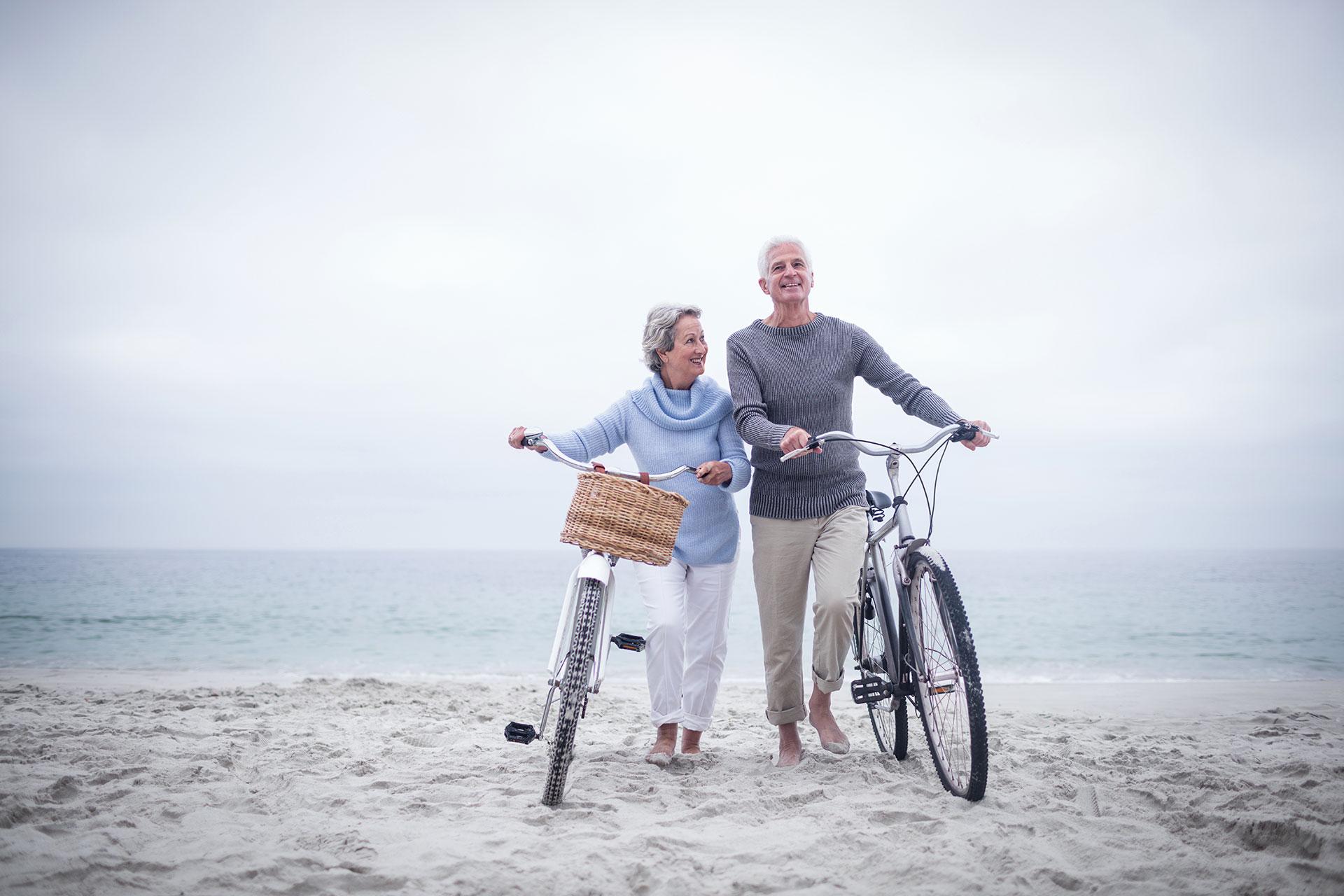 Informieren Sie sich jetzt und betreiben Sie Vorsorge für sich und Ihren Körper – Eine ältere Dame und ein älterer Herr spazieren mit Ihren Fahrrädern am Stand